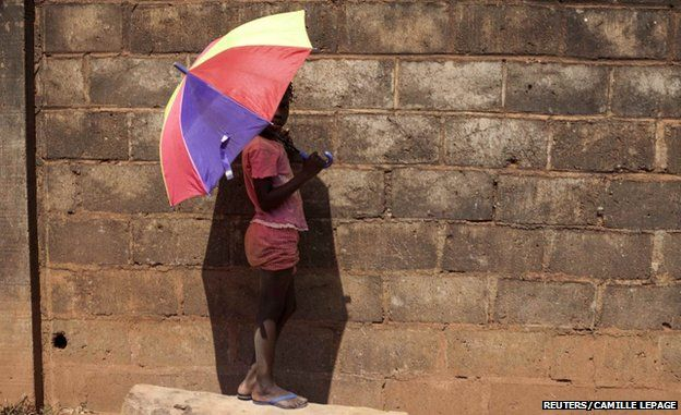 A girl holds an umbrella in Bangui (9 March 2014)