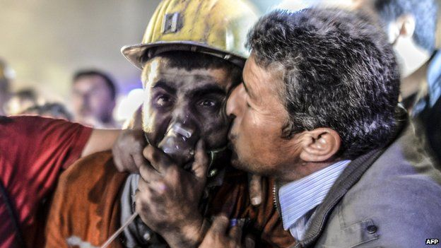 Man kisses son after his rescue from the mine in Soma, Manisa, Turkey, on 13 May 2014