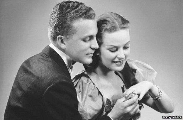 Historical image of a newly engaged couple looking at ring on woman's finger