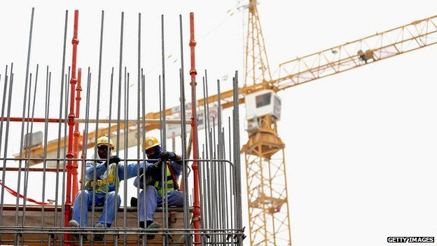Construction workers put up scaffolding on a building site in Doha, Qatar - 10 May 2014