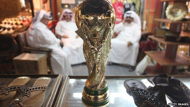 Arab men at a shoemaker's stall in a market in Doha, Qatar, with a replica of the FIFA World Cup trophy - 24 October 2011