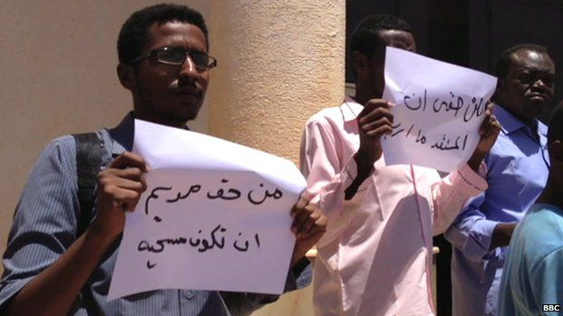 """Protesters outside the court in Khartoum hold banners saying """"Meriam has the right to be Christian"""" and """"I have the right to choose any religion"""" - 15 May 2014"""