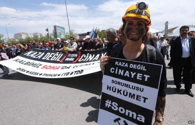 """A woman at a protest in Ankara dressed as a miner holds a sign reading: """"This is not an accident, this a murder. The government is responsible."""""""