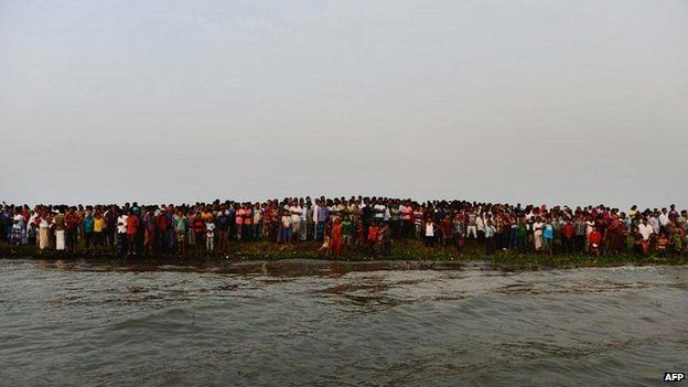 Local residents gather on the bank of the Meghna river to await news of the missing passengers - 15 May 2014