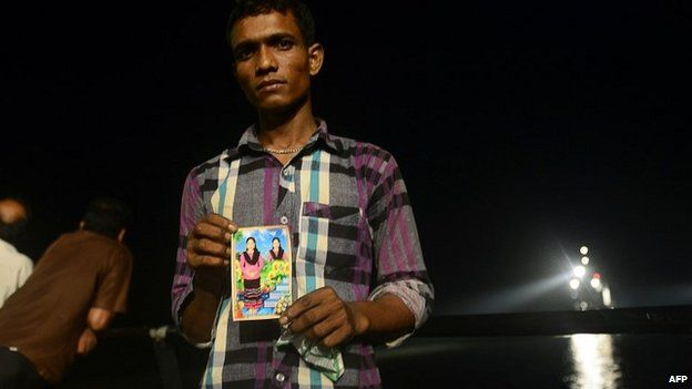 A relative holds a photograph of his missing niece as rescue workers continue the search for survivors - 15 May 2014