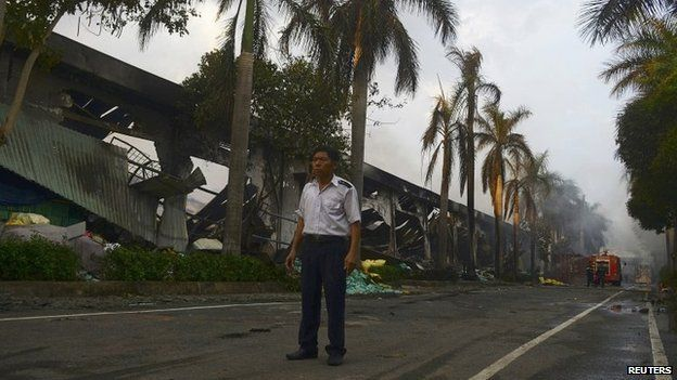 A security guard stands near a damaged Chinese owned shoe factory in Vietnam's southern Binh Duong province on 14 May 2014