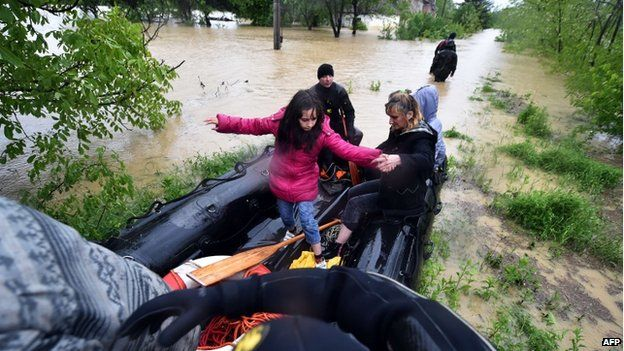 Serbian police officers evacuate people from their homes surrounded by flood waters near the town of Lazarevac, on 15 May 2014