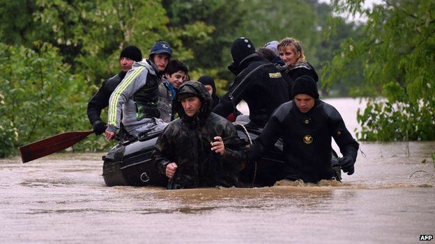 Serbian police officers evacuate people from their homes surrounded by flood waters near the town of Lazarevac, south of Belgrade, on 15 May 2014.