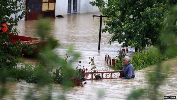 A man stands in his flooded garden in front of his house in the town of Lazarevac, south from Belgrade, on 15 May 2014.