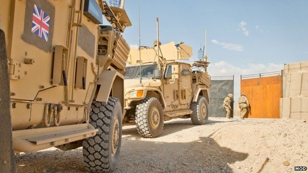 Two armoured vehicles leaving or entering a base as a soldier closes the gates in the background