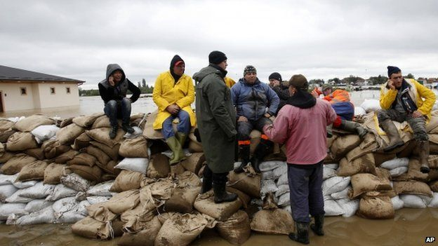 People rest on a dam of sandbags by Sava river at Sremska Mitrovica, 90km west of Belgrade 17/05/2014