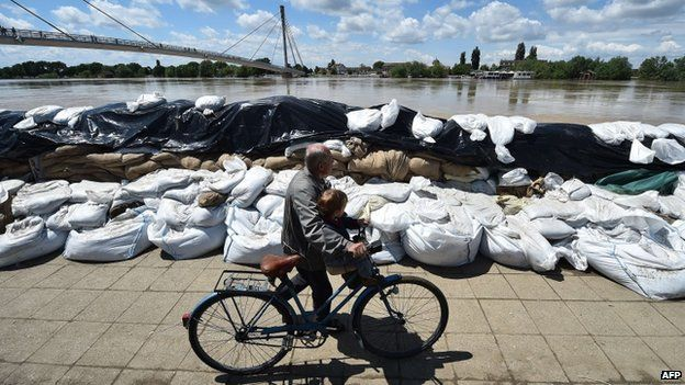 A man pushes a bicycle past sand bags protecting the banks of the Sava river in Sremska Mitrovica on 18 May 2014