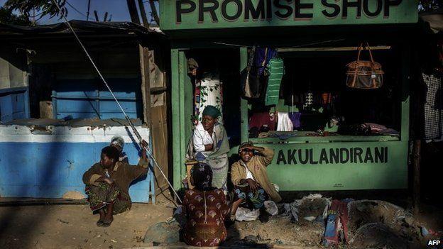 Malawian women sit outside a shop in a market of a shanty town, on 18 May 2014 in Blantyre, Malawi