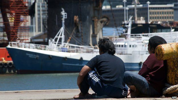 Two of the 75 Indonesian fishermen living on seven rusted Taiwanese-registered fishing boats sit at Cape Town Harbour on 28 November, 2013