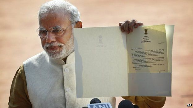 Narendra Modi displays the letter from the Indian President inviting him to form the new government