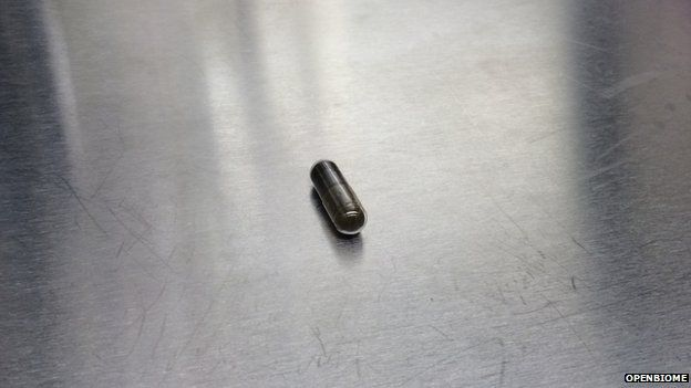 A brown capsule on a steel table