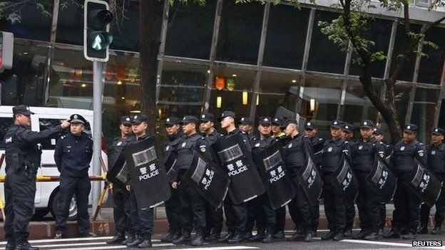Policemen with riot gear gather as they block a street leading to the site of an explosives attack, in downtown Urumqi, Xinjiang Uighur Autonomous Region, 23 May 2014