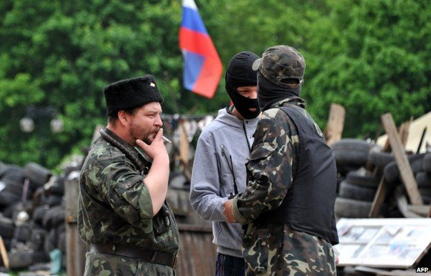 """Pro-Russian militants stand by as they maintain a barricade outside the regional state building in the eastern Ukrainian city of Donetsk on May 12, 2014. A presidential election in Ukraine scheduled for May 25 that the West sees as vital to restoring order """"will not happen"""" in the Donetsk region, the self-styled governor of the province Denis Pushilin said Monday."""