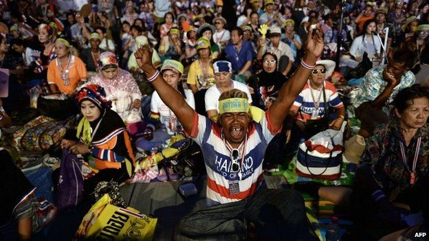 """Thai anti-government protesters celebrate at their camp outside Government House after Thailand""""s army chief announced that the armed forces were seizing power, in Bangkok on May 22, 2014."""