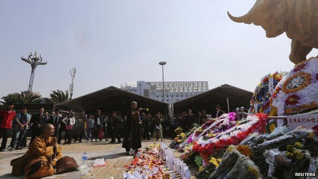 Buddhist monks pray in front of offerings and wreathes for the victims of a knife attack last Saturday, at Kunming Railway Station in Kunming, Yunnan province 7 March 2014. At least 29 people were killed and police shot dead four of the attackers.