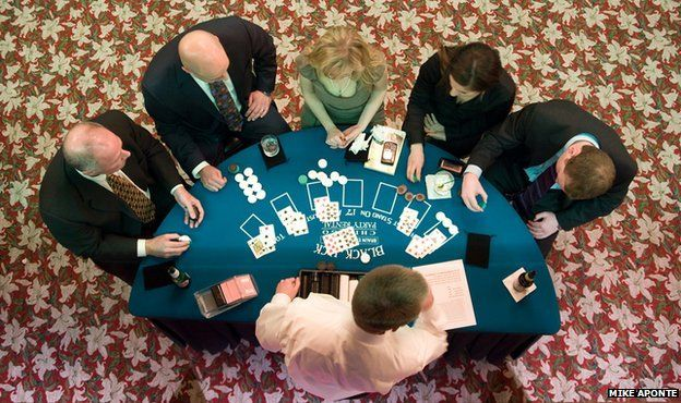 People standing round a blackjack table