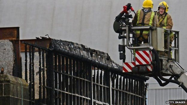 Firefighters beside burnt-out building