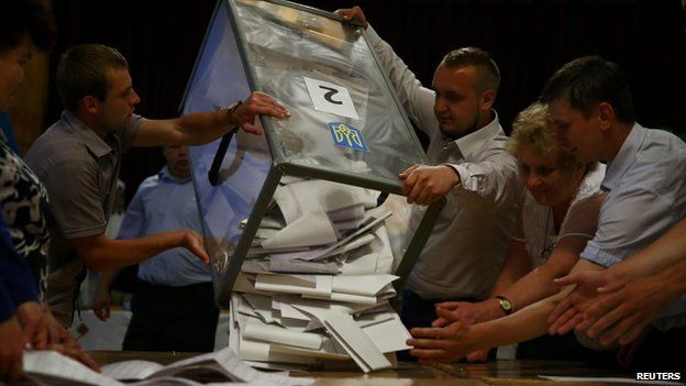 Members of the election commission empty ballot boxes in a polling station in the town of Rohatyn in western Ukraine on 25 May 2014.