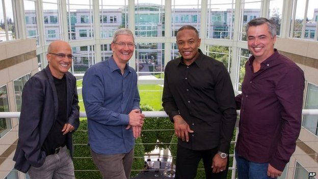 In this image provided by Apple, from left to right, music entrepreneur and Beats co-founder Jimmy Iovine, Apple CEO Tim Cook, Beats co-founder Dr. Dre, and Apple senior vice president Eddy Cue pose together at Apple headquarters in Cupertino, Calif.,