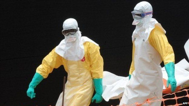 People carry the body of a person killed by Ebola at a medical centre in Guekedou, Guinea - 1 April 2014