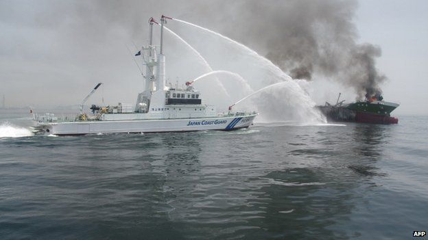 """This handout picture taken and released by Japan""""s Coast Guard on 29 May 2014 shows a Coast Guard boat (L) fighting a fire onboard the 998-tonne oil tanker Shoko-Maru (R) off the coast of Hyogo prefecture, around 450 kilometres (280 miles) west of Tokyo"""