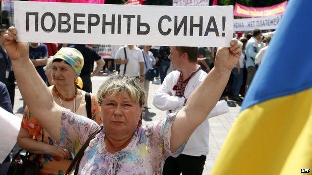 """A Ukrainian woman holds up a banner reading """"bring back my son"""" at a rally with other relatives of Ukrainian officers and soldiers in Kiev (29 May 2014)"""