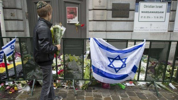 A Jewish boy stands with flowers in front of an Israeli flag and flowers laid in front of the Jewish Museum in Brussels on 26 May 2014