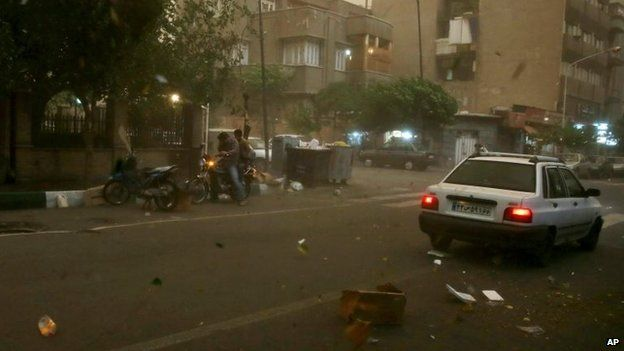 A motorbike and a car, seen through the window of a car, are stopped in a street in Tehran, Iran, 2 June 2014