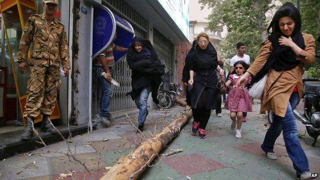 Pedestrians make their way on a sidewalk of Tehran, Iran, 2 June 2014