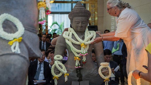An assistant places traditional Cambodian crowns of flowers around the neck of the Balarama statue returned by Christie's auction house during an unveiling ceremony on 3 June, 2014 in Phnom Penh, Cambodia