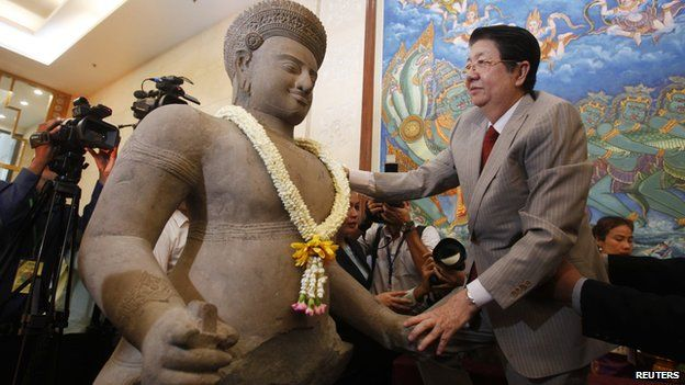 Deputy Prime Minister Sok An places a garland on an ancient artefact which are recently returned to the country during a ceremony at the Council of Ministers in Phnom Penh on 3 June, 2014
