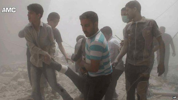 Syrian citizens carrying a man who was injured by a government forces airstrike, in Aleppo, Syria, on 4 June 2014