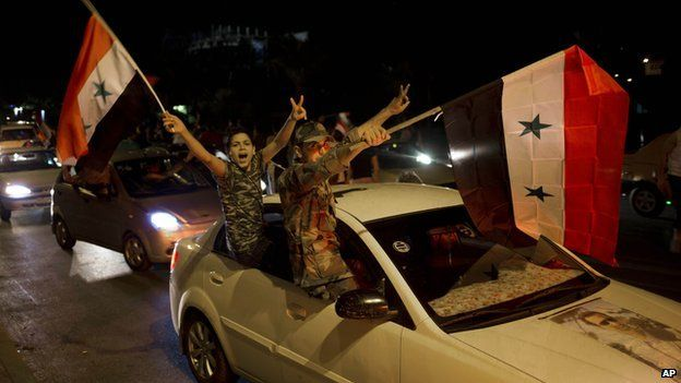 Syrian soldiers celebrate Bashar al-Assad's presidential re-election in Damascus on 4 June 2014