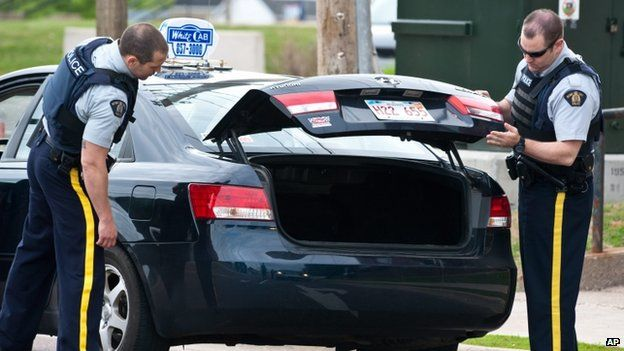 Royal Canadian Mounted Police check the trunk of a taxi at a roadblock in Moncton, New Brunswick, on 5 June 2014