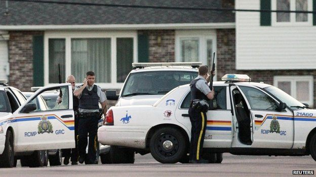 RCMP officers take cover behind their vehicles in Moncton, New Brunswick, on 4 June 2014