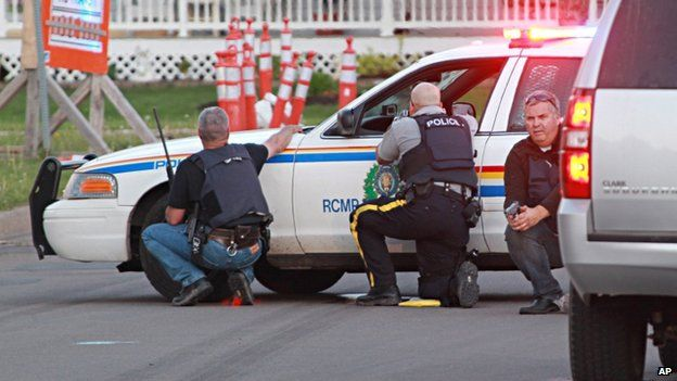 Police officers take cover behind their vehicles in Moncton, New Brunswick, on 4 June 2014
