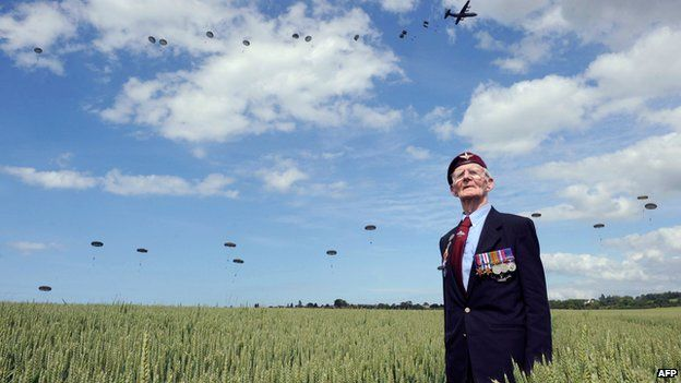 Veteran Frederick Glover posing for a photograph as soldiers parachute in Ranville