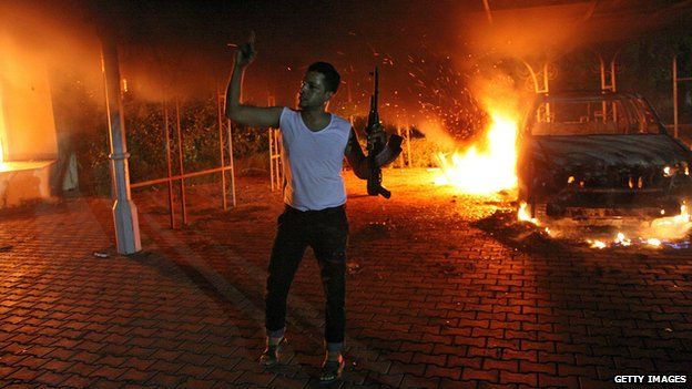 A militant brandishing a gun poses in front of a burning vehicle inside the US consulate compound in Benghazi, Libya late on September 11, 2012