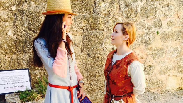 Two women dressed in medieval clothes, one of them on a mobile phone