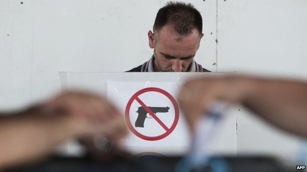"""A Kosovo Albanian man prepares his ballot at a polling booth with a """"no guns"""" sign before voting at a polling station in Pristina on June 8,"""