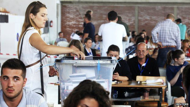 A Kosovo Albanian woman places her ballot paper into a voting box at the polling station in the capital city Pristina June 8