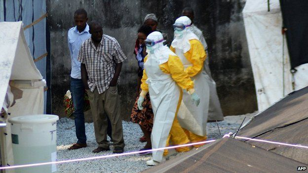 Health workers, wearing protective suits, walking in an isolation centre for people infected with Ebola at Donka Hospital in Conakry on 14 April 2014