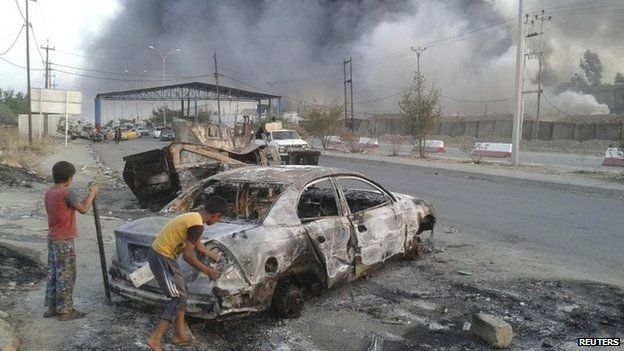 Iraqi children stand next to a vehicle destroyed during clashes between Sunni militants and Iraqi security forces in Mosul (10 June 2014)