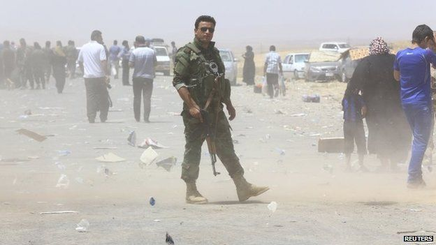 A member of the Kurdish security forces stands guard at a checkpoint on the outskirts of Arbil (10 June 2014)