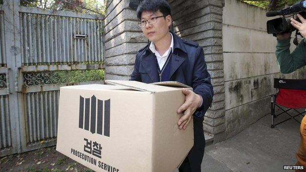 """An official from the Incheon District Prosecutors"""" office carries a box during a raid of the home of Yoo Byung-un, in Seoul on 23 April, 2014"""